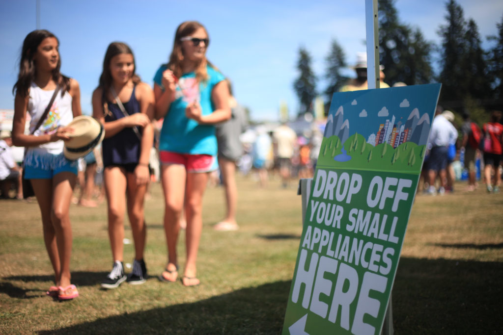 Kids walking past a RecycleFest sign. Repair Matters will be attending RecycleFest 2019