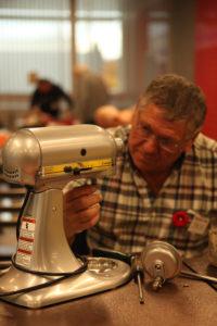 volunteer repairing stand mixer