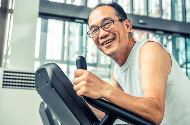 Smiling man exercises on spin machine
